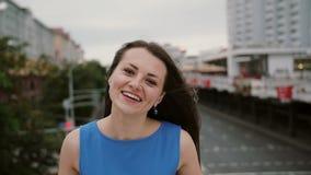 Het glimlachen bekijkt de mooie meisje status op de brug, wat betreft haar haar en de camera De wind blaast haar lang haar stock video