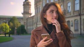 Het glimlachen bevindt het Kaukasische brunette zich en scrolt haar telefoon met ontspannen gezicht op stedelijk gebied, zonnige  stock footage