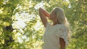 Het glimlachen blond gekleed in een kleding die in het bos rusten stock video