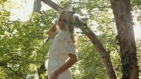 Het glimlachen blond gekleed in een kleding die in het bos rusten stock footage