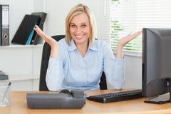 Het glimlachen blonde vrouwenzitting achter bureau stock foto's