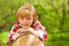 Het glimlachen blonde zeven jaar oude jongens die op een logboek leggen Royalty-vrije Stock Afbeelding