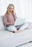 Het glimlachen blondezitting op laag die laptop met behulp van royalty-vrije stock afbeelding
