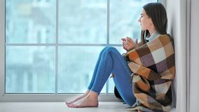 Het glimlachen blootvoetse vrouwenzitting op vensterbank die op de winterweer kijken stock footage