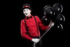 het glimlachen bootst holdingsbundel van zwarte ballons na stock foto