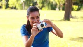 Het glimlachen brunette die beelden in het park nemen stock video