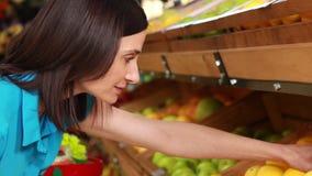 Het glimlachen brunette die citroenen in het winkelen mand zetten stock videobeelden