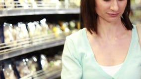 Het glimlachen brunette die met kruidenierswinkellijst winkelen stock videobeelden