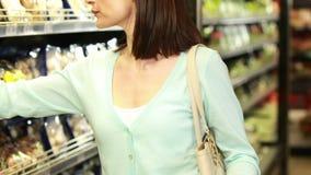 Het glimlachen brunette die met kruidenierswinkellijst winkelen stock video