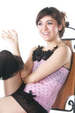 Het glimlachen brunette in roze zitting op stoel Stock Foto