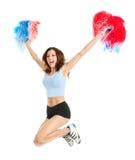 Het glimlachen cheerleader meisje het stellen met pom poms Stock Afbeeldingen