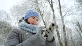 Het glimlachen de berichten van de vrouwenlezing op de telefoon in de winterpark stock videobeelden