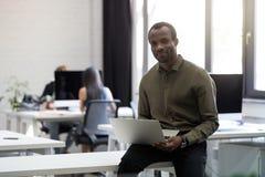 Het glimlachen de gelukkige zitting van de afro Amerikaanse zakenman op zijn bureau royalty-vrije stock afbeelding