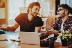 Het glimlachen de Kerels gebruiken binnen Laptops terwijl Coworking stock foto