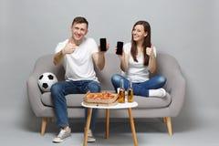 Het glimlachen de man van de paarvrouw de voetbalfans juichen steun omhoog favoriet team toe die mobiele telefoon met het lege le stock foto