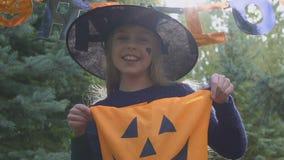 Het glimlachen de truc van de meisjesholding of behandelt zak, Halloween-spelvoorbereiding, traditie stock video