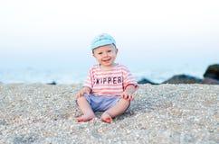 Het glimlachen de zitting van de babyjongen op het zand dichtbij overzees Het concept van de zomer Vakantie het ontspannen, stran stock foto