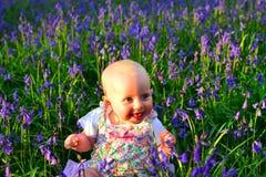 Het glimlachen de zitting van het babymeisje op een overweldigend gebied van klokjes stock fotografie