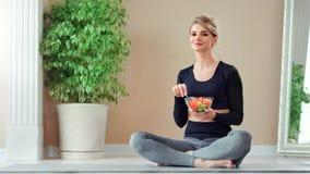 Het glimlachen de zitting van de geschiktheidsvrouw in lotusbloempositie die verse groentesalade eten die vork gebruiken stock footage