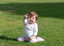 Het glimlachen de zitting van het babymeisje op een gras Royalty-vrije Stock Foto's