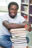 Het glimlachen de Zitting van Studentenwith stacked books binnen Royalty-vrije Stock Foto's