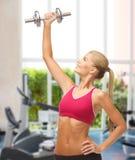 Het glimlachen domoor van het vrouwen de opheffende staal bij gymnastiek Stock Afbeeldingen