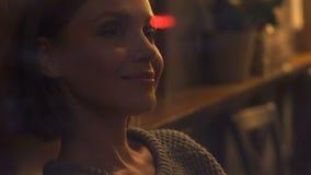 Het glimlachen donkerbruine vrouwelijke zitting in cafetaria, kijkend door venster, het dromen stock videobeelden