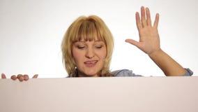 Het glimlachen drukken de gelukkige vrouw status erachter en het leunen op een wit leeg aanplakbord of een aanplakbiljet, verschi stock videobeelden