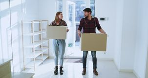 Het glimlachen en het voelen wekten een nieuw echtpaar op die tot een nieuw ruim huis leiden zij het bewegende dag dragen hebben stock videobeelden