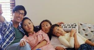Het glimlachen familie het ontspannen op bank in woonkamer 4k stock videobeelden