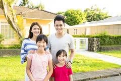 het glimlachen familieportret buiten hun huis royalty-vrije stock afbeeldingen