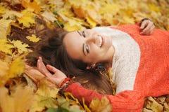 Het glimlachen gelukkig womanlportret, die in de herfstbladeren liggen royalty-vrije stock afbeeldingen