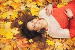 Het glimlachen gelukkig womanlportret, die in de herfstbladeren liggen stock foto's