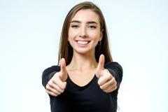 Het glimlachen het gelukkige jonge donkerbruine vrouw beduimelt tonen omhoog gebaar Stock Afbeeldingen