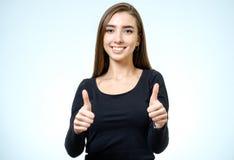 Het glimlachen het gelukkige jonge donkerbruine vrouw beduimelt tonen omhoog gebaar Royalty-vrije Stock Afbeelding