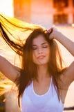 Het glimlachen geniet van het mooie jonge vrouwenportret in de zonsondergangzomer royalty-vrije stock afbeelding