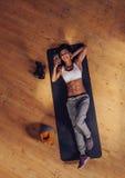 Het glimlachen geschiktheid het vrouwelijke gebruiken mobiel in gymnastiek Royalty-vrije Stock Afbeeldingen