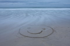 Het glimlachen gezicht trok op strand Stock Foto
