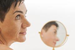 Het glimlachen gezicht van vrouw met spiegel Stock Foto