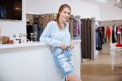Het glimlachen het aantrekkelijke jonge vrouwenwinkel hulp stading in kledingsopslag Stock Afbeelding