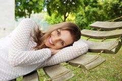 Het glimlachen het aantrekkelijke vrouw ontspannen op hangmat buiten stock foto's
