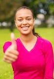 Het glimlachen het Afrikaanse Amerikaanse vrouw omhoog beduimelt tonen Stock Fotografie