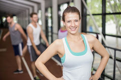 Het glimlachen het atletische vrouw stellen met handen op heupen royalty-vrije stock fotografie