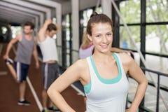 Het glimlachen het atletische vrouw stellen met handen op heupen stock afbeeldingen