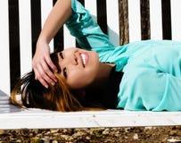 Het glimlachen het Aziatische Amerikaanse Vrouw Doen leunen op Bank in openlucht Stock Afbeeldingen