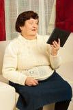 Het glimlachen het bejaarde bekijken fotoframe Stock Afbeeldingen