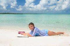 Het glimlachen het blije gelukkige meisje ontspannen op wit zand mooi strand tegen oceaan en blauwe hemelachtergrond Stock Fotografie
