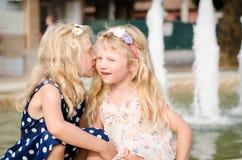 Het glimlachen het blonde meisjes fluisteren stock fotografie