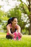 Het glimlachen het geschikte bruine haar uitrekken zich in het gras Stock Foto's