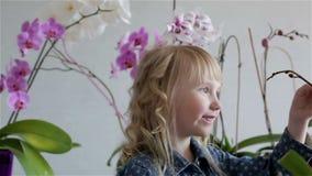 Het glimlachen het gezicht van het kindmeisje dichtbij purpere en witte orchideeën stock video